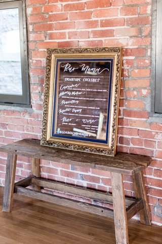 wedding-reception-bar-menu-on-mirror-gold-frame-beer-wine-tequila-calligraphy-signature-cocktails