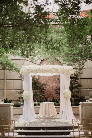 wedding-ceremony-outside-at-hotel-white-chuppah-and-ivory-flowers-on-top-and-on-sides-altar