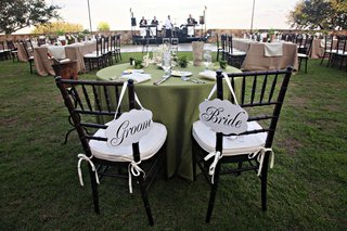 wood-chairs-with-white-cushions-and-bride-and-groom-signs