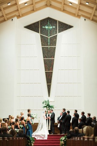 bride-and-groom-at-altar-top-of-red-stairs-guests-in-church-pews-wedding-party-tall-ceiling-wood