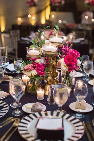 floating-candles-on-gold-stands-bright-pink-roses-black-and-white-wedding-decor