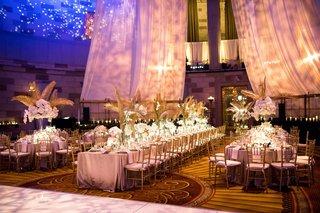 wedding-reception-long-round-table-gold-palm-leaves-drapery-blue-lighting-dance-floor-ballroom