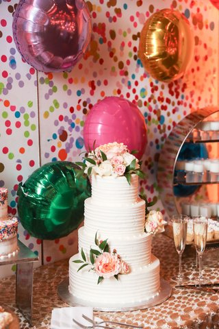 four-layer-wedding-cake-with-fresh-blush-flowers-on-dessert-table-with-helium-balloons-confetti