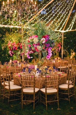 tent-wedding-reception-with-gold-rosette-table-linens-tall-green-flower-arrangements-string-lights