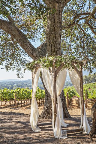 outdoor-wedding-ceremony-small-four-post-wood-arbor-with-greenery-ivory-drapery-curtains-under-tree