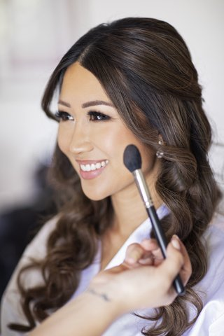 bride-with-hair-down-curls-natural-makeup-pretty-eyelashes-makeup-artist-with-blush-brush