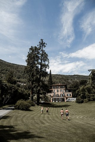 groom-and-groomsmen-running-on-lawn-at-lake-como-villa-after-jumping-in-lake-before-wedding