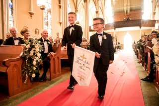 ring-bearers-in-tuxedos-ring-bearer-in-glasses-with-banner