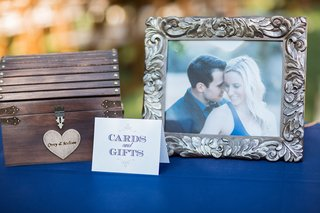 outdoor-wedding-reception-gift-table-covered-in-royal-blue-tablecloth-wood-chest-framed-photo