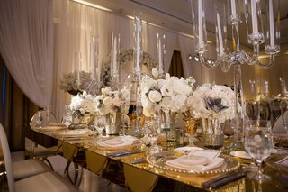 gold-mirror-table-with-white-chairs-low-ivory-flower-arrangements-and-tall-crystal-candelabra-taper