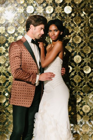bride-in-inbal-dror-mermaid-gown-groom-in-bronze-patterned-tuxedo-jacket-golden-wall-as-backdrop