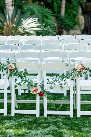 white-ceremony-chairs-draped-with-rose-and-greenery-garland