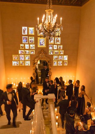 guests-in-formal-attire-walk-up-staircase-of-the-plaza-hotel-with-projected-picture-frames-on-wall
