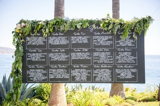 oceanfront-wedding-reception-with-chalkboard-seating-chart-with-greenery-white-pink-flowers