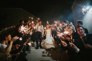 alex-kuznetsov-wedding-day-grand-exit-groom-holds-sparkler-during-wedding-grand-exit