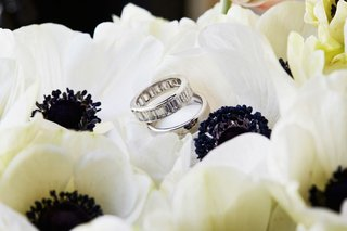 wedding-ring-with-diamonds-and-polished-ring-on-top-of-japanese-anemone-flowers