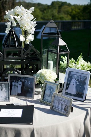 black-and-white-pictures-from-family-members-weddings-displayed-in-frames-on-guestbook-table-flowers