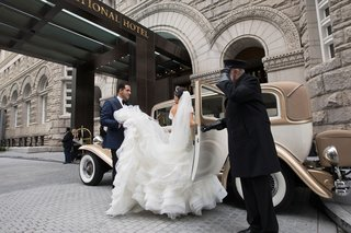 driver-opening-door-for-bride-in-voluminous-gown-groom-holding-skirt-classic-car