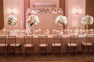 long-reception-table-pink-white-tall-small-centerpieces-flower-structure-greenery-gold-chairs