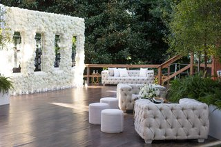 wedding-cocktail-hour-lounge-area-tufted-chesterfield-sofa-ottoman-flower-seating-chart-mirror-names