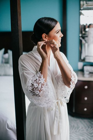 bride-with-slick-hairstyle-low-bun-putting-on-earrings-white-robe-lace-flower-motif-sleeves