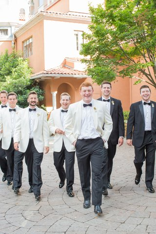 groom-in-ivory-suit-jacket-and-black-bow-tie-with-matching-groomsmen-tuxedo-shoes