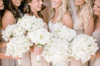 bridesmaid-with-neutral-dresses-and-bouquets-of-white-peonies-sweet-peas-freesias