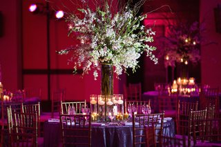 wedding-reception-with-a-tall-centerpiece-tion-tablof-white-orchids-surrounded-by-floating-candles