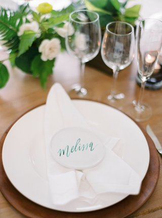 wedding-reception-wood-table-low-centerpiece-flowers-white-plate-white-napkin-white-place-card