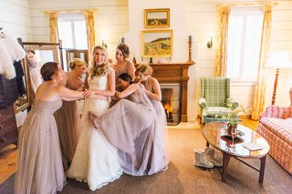 bridesmaids-playfully-help-bride-into-her-wedding-dress-while-laughing