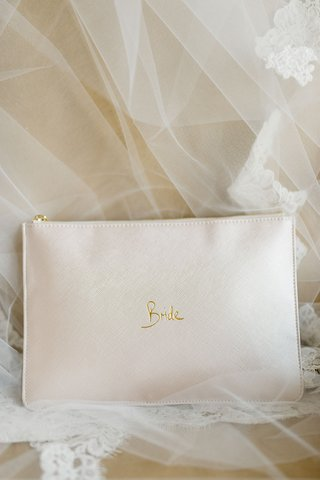wedding-accessories-leather-clutch-with-gold-bride-and-zipper-on-chair-with-veil