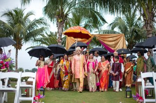 indian-american-groom-walks-into-ceremony-with-family-holding-umbrellas-due-to-rain