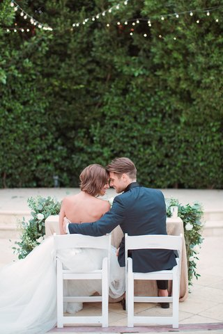 bride-in-an-anne-barge-wedding-dress-sits-with-groom-in-a-teal-tuxedo-jacket-at-garden-reception