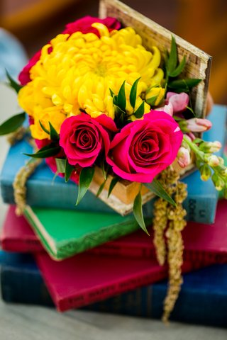 yellow-mum-small-magenta-roses-stack-of-colorful-books