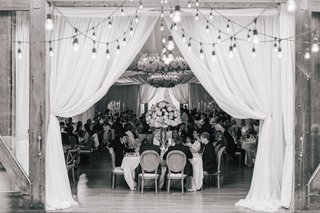 black-and-white-photo-of-guests-enjoying-reception-drapery-flower-chandelier-patio-string-lights