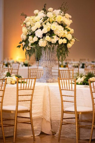 large-stone-vase-with-ivory-flowers-and-dark-greenery-in-the-center-of-intersecting-tables-with