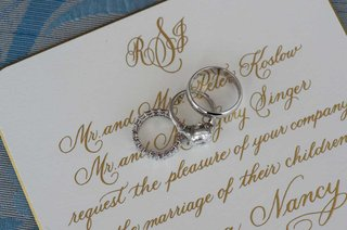 brides-diamond-engagement-ring-and-wedding-band-and-grooms-platinum-wedding-band-on-invitation