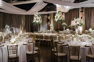 white-and-gold-tablescapes-with-tall-floral-arrangements-and-cascading-fabric-hanging-over-space