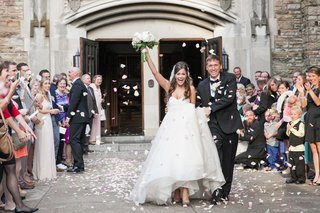 friends-and-family-throw-flower-petals-at-the-newlyweds-as-they-leave-their-church-ceremony