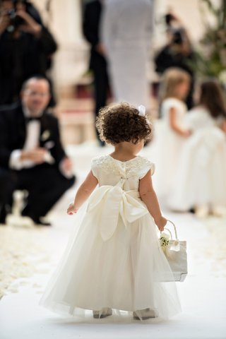 curly-haired-flower-girl-with-basket-walks-up-the-aisle