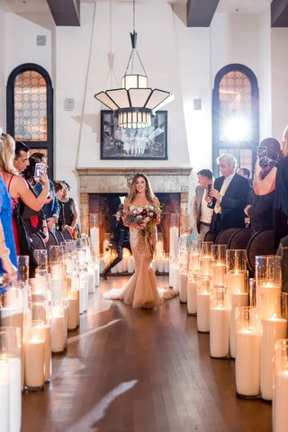bride-in-blush-inbal-dror-wedding-dress-fall-bouquet-candle-lined-aisle-guests-taking-phone-photos