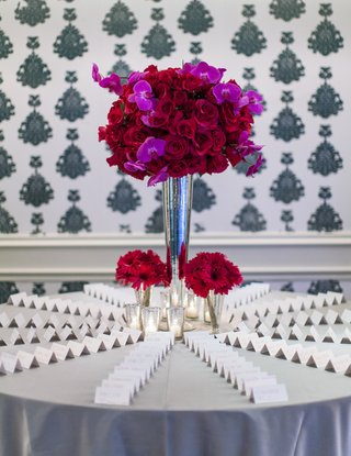 escort-cards-on-silver-table-with-red-and-fuchsia-flower-arrangement
