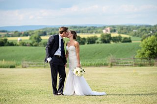 bride-in-a-berta-bridal-gown-kisses-groom-in-a-navy-ralph-lauren-tuxedo-on-a-pennsylvania-field