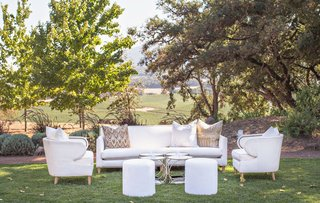 outdoor-wedding-reception-white-sofa-and-armchair-ottoman-with-collection-of-four-side-tables