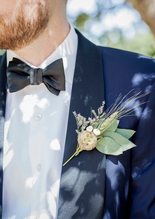 groom-in-navy-blue-tuxedo-with-black-lapels-and-rustic-herb-leaf-boutonniere