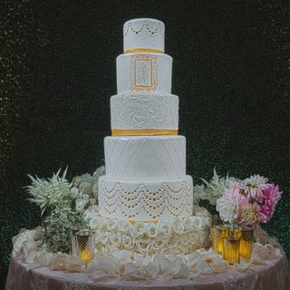 white-and-gold-wedding-cake-five-layers-with-different-designs-and-monogram