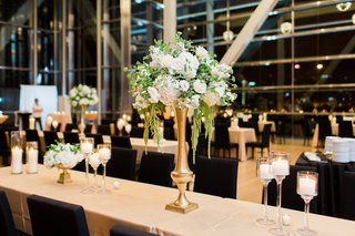 tall-centerpiece-with-white-hydrangeas-greenery-and-amaranths-gold-base-long-table