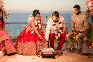 bride-in-lehnga-and-groom-in-sherwani-mandap-indian-wedding-traditions-pacific-ocean-view