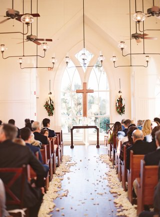 chapel-wedding-church-pews-with-cross-and-magnolia-leaves-on-either-side-white-flower-petals-floor