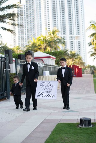 ring-bearers-holding-hands-in-tuxedos-bow-ties-acqualina-resort-and-spa-florida-outside-wedding